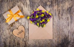 A small gift with a gold ribbon, an envelope with flowers and a heart. Romantic concept. Royalty Free Stock Photo
