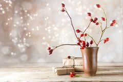 Small gift parcels and rosehip branches on a rustic wooden table Royalty Free Stock Image