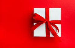 Small gift with red bow on red. Background. Space for your text Stock Photos