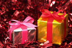 Small gifts on red tinsel. Royalty Free Stock Photography