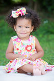 Small  girl with an afro hairstyle sitting on the grass Royalty Free Stock Image