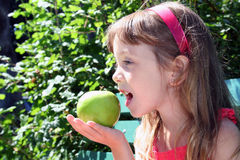 Small girl with apple. The profile of a small girl in a red dress as she eats an apple outside in the sunshine Royalty Free Stock Images