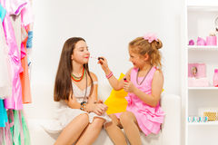 Small girl applying lip gloss on her friend Royalty Free Stock Photography