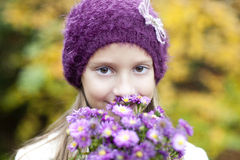 Small girl with autumn's flowers Stock Image