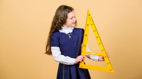 Small girl back to school. STEM school disciplines. Pupil girl with big ruler. math lesson. Education and knowledge. School student learning geometry stock photos