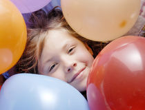 Small Girl and balloons. A small girl surrounded with balloons royalty free stock images