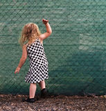 Small girl banging on a green fence. Young girl behind a green meshed fence royalty free stock images