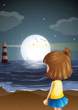 A small girl at the beach watching the lighthouse Royalty Free Stock Photography