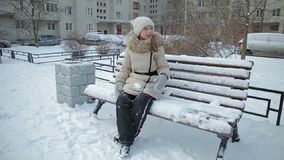 Small girl on bench snowfall slow motion stock video footage