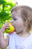 Small girl bite off juicy big apple Royalty Free Stock Photo