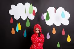 A small girl on a black background with clouds and raindrops. Royalty Free Stock Photo