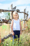 Small girl with blond hair standing in front of fence Royalty Free Stock Photos