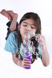 Small girl blowing bubbles. Lying on floor, part asian - Scandinavian descent royalty free stock images