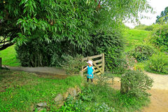Small girl in blue dress passing through Hobbiton village gate Stock Photos
