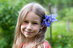 Small girl with blue iris flower in her hair Royalty Free Stock Photography
