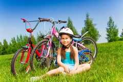 Small girl in blue shirt sits on a meadow Royalty Free Stock Image