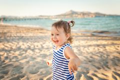Cute girl on a beach on sunset. Mallorca, Spain. Small girl in blue and white striped shirt and white shorts having fun on a beach on sunset. Mallorca, Spain stock images