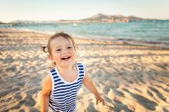 Cute girl on a beach on sunset. Mallorca, Spain. Small girl in blue and white striped shirt and white shorts having fun on a beach on sunset. Mallorca, Spain royalty free stock photography