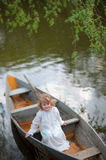 Small girl in the boat at the river Stock Photos