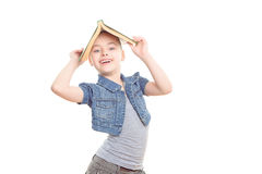Small girl with a book. Portrait of a small girl holding a big green book above her head like a house smiling wearing a grey t-shirt and jeans jerkin ,isolated Stock Photo