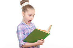 Small girl with a book. Portrait of a small girl holding a big green book reading it looking very excited with her mouth wide opened wearing colorful checkered Royalty Free Stock Photography