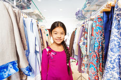 Small girl with braid between clothes hangers Royalty Free Stock Images