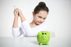 Small girl breaking piggy. Bank Stock Photography