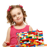 Small girl builds a house from plastic blocks Royalty Free Stock Photos