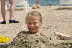 Small girl buried in the sand Stock Photography