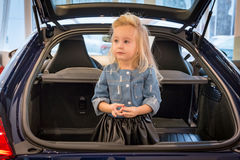 Small girl in car exhibition room Royalty Free Stock Images