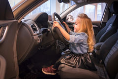 Small girl in car exhibition room Royalty Free Stock Photo