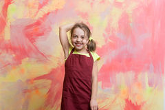 Small girl chef with happy face in cook apron. Small baby girl or cute child with happy face in red chef or cook apron on colorful abstract background Royalty Free Stock Photos