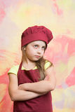 Small girl chef with serious face in hat and apron Royalty Free Stock Photography