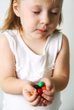 Small girl chews the candies Stock Photos