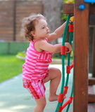 Small girl child climbing up. On children activity ladder outdoors Stock Photos
