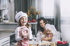 Small girl child eats a donut with my mom and sister happy cook stock photo