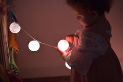 Small girl with Christmas tree lights stock photo