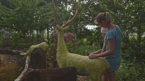 Small Girl Climbs on Deer Sculpture in Tropical Park. Small girl in striped dress white panama climbs on yellow stone deer sculpture in tropical park mother stock video footage