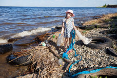 Small girl collecting rubbish. Near the river Stock Photography