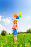 Small girl with colorful balloons wearing circlet. In summer Royalty Free Stock Photos