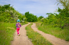 Small girl in a colorful outfit on a country track Stock Images