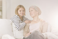 Small girl comforting ill mother. In her battle with cancer Stock Photography