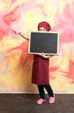 Small girl cook in hat with blackboard. Royalty Free Stock Images