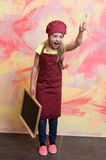 Small girl cook in hat with blackboard. Royalty Free Stock Image