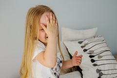 Small girl is covering her face by hand. The little girl covers her face with one hand. Peekaboo. Children`s emotions royalty free stock photos