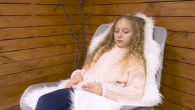 Small girl in cozy chair. Beautiful teenage girl sitting in cozy chair. Curly haired girl in warm sweater at home stock video