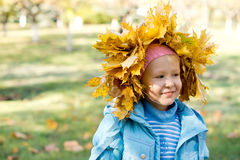 Small girl in a crown of autumn leaves Stock Photos