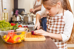 Small girl cutting onion on the kitchen counter Royalty Free Stock Images