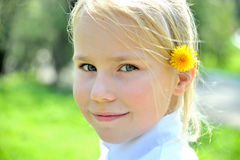Small girl with dandelion behind her ear. Looking on camera Stock Photography