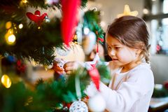Small girl decorating Christmas tree. Royalty Free Stock Photos